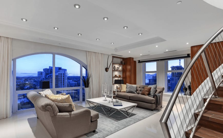 The white tray ceiling is complemented by the large dome window on the side that features an amazing over-looking view of the city. The pair of gray couches flanking the modern white-top coffee table is marked by the gray area rug.