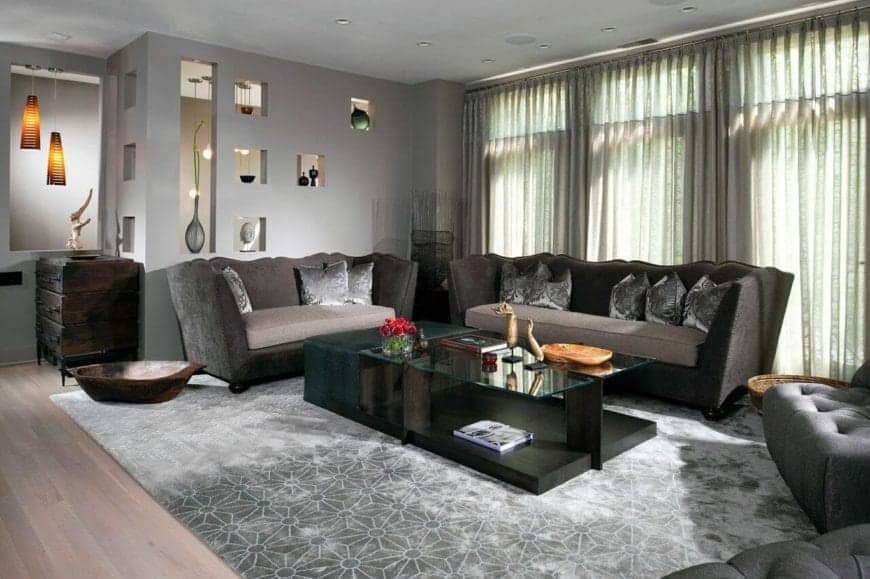 The brilliant tall windows behind the gray velvet sofa set appears gray combined with the natural lights making it match the gray walls and light gray area rug underneath the modern glass coffee table that has a dark wooden body.