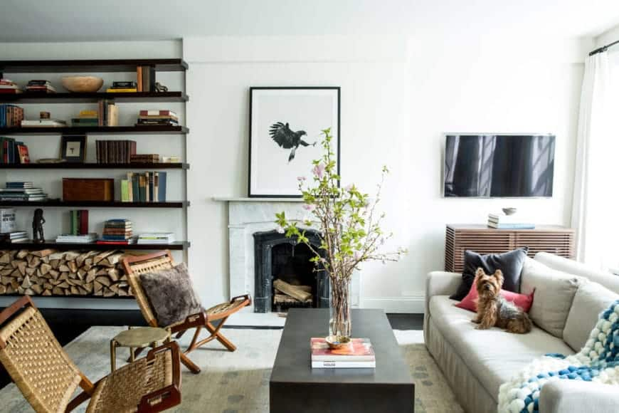 This simple living room has a traditional fireplace with a white marble mantle beside the built-in shelves  with books and decorations and the lowest shelf for the firewood. This setup is paired with a white sofa facing a pair of rustic woven wicker chairs and a dark wooden coffee table.