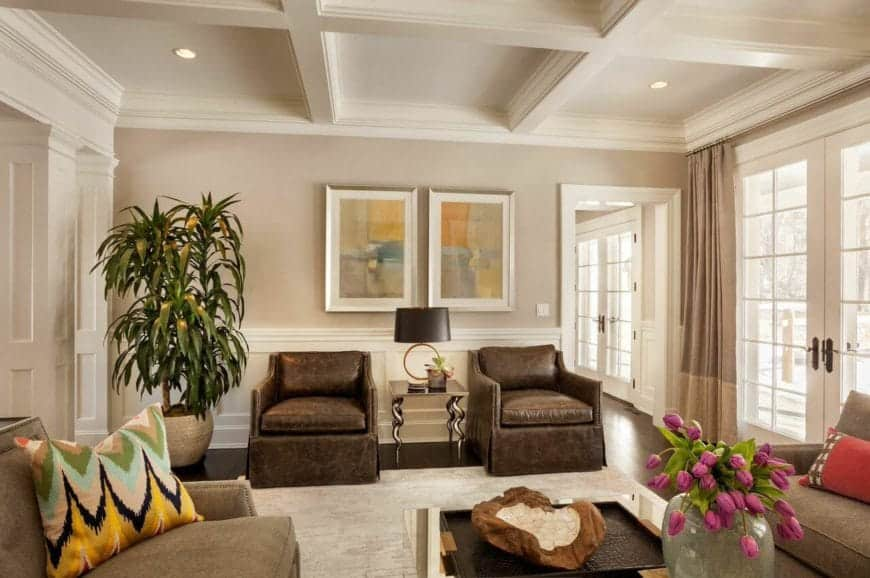 The white tray ceiling is perfectly paired with beige walls that has white wainscoting and adorned with a couple of colorful paintings mounted above the brown leather armchairs that matches with the hardwood flooring.