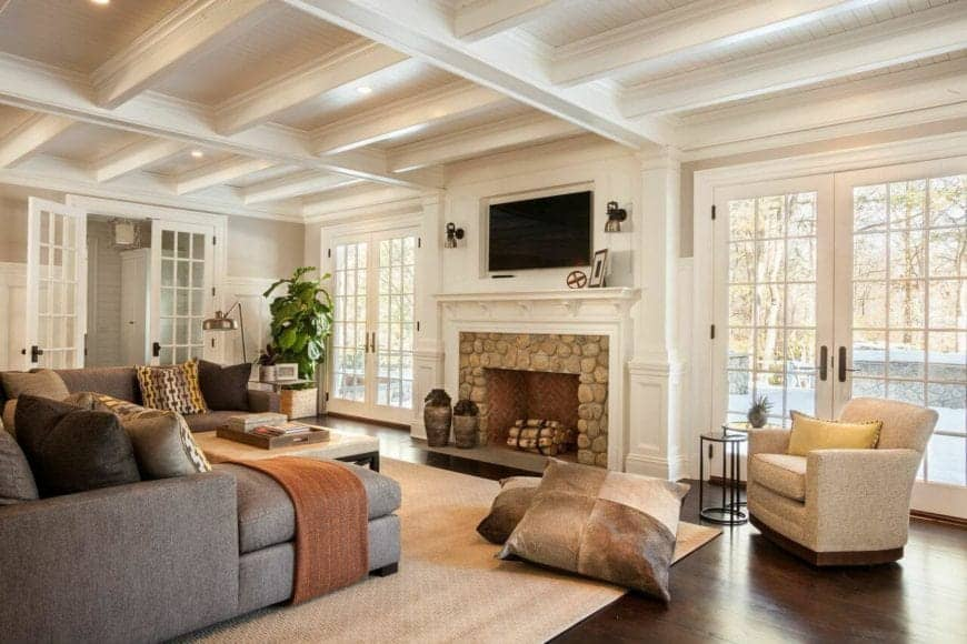 The large gray sectional couch is facing the fireplace inlaid with beige stone and has a white mantle that blends in with the white walls and white tray ceiling that is contrasted by the dark hardwood flooring.