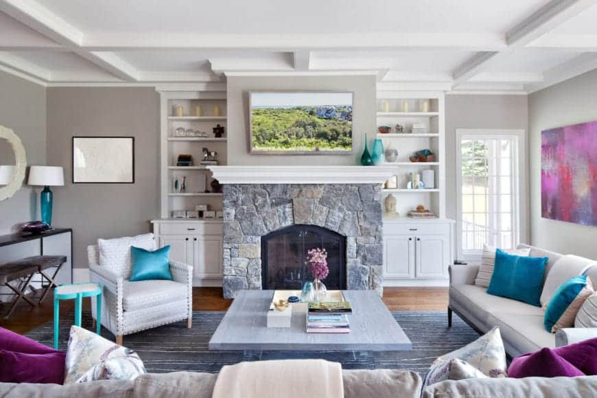 This gorgeous living room has a white tray ceiling paired with light gray walls and hardwood flooring. There are splashes of color around the room like the colorful painting, blue <a class=