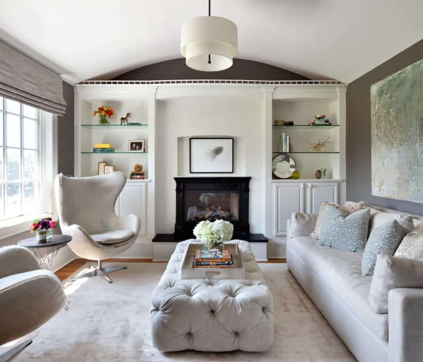 The white cove ceiling is paired with a wall dominated by a white wooden structure that houses the fireplace with black mantle that is flanked with built-in shelves and cabinets. This is a complement to the light gray sofa and the couple of wingback chairs.