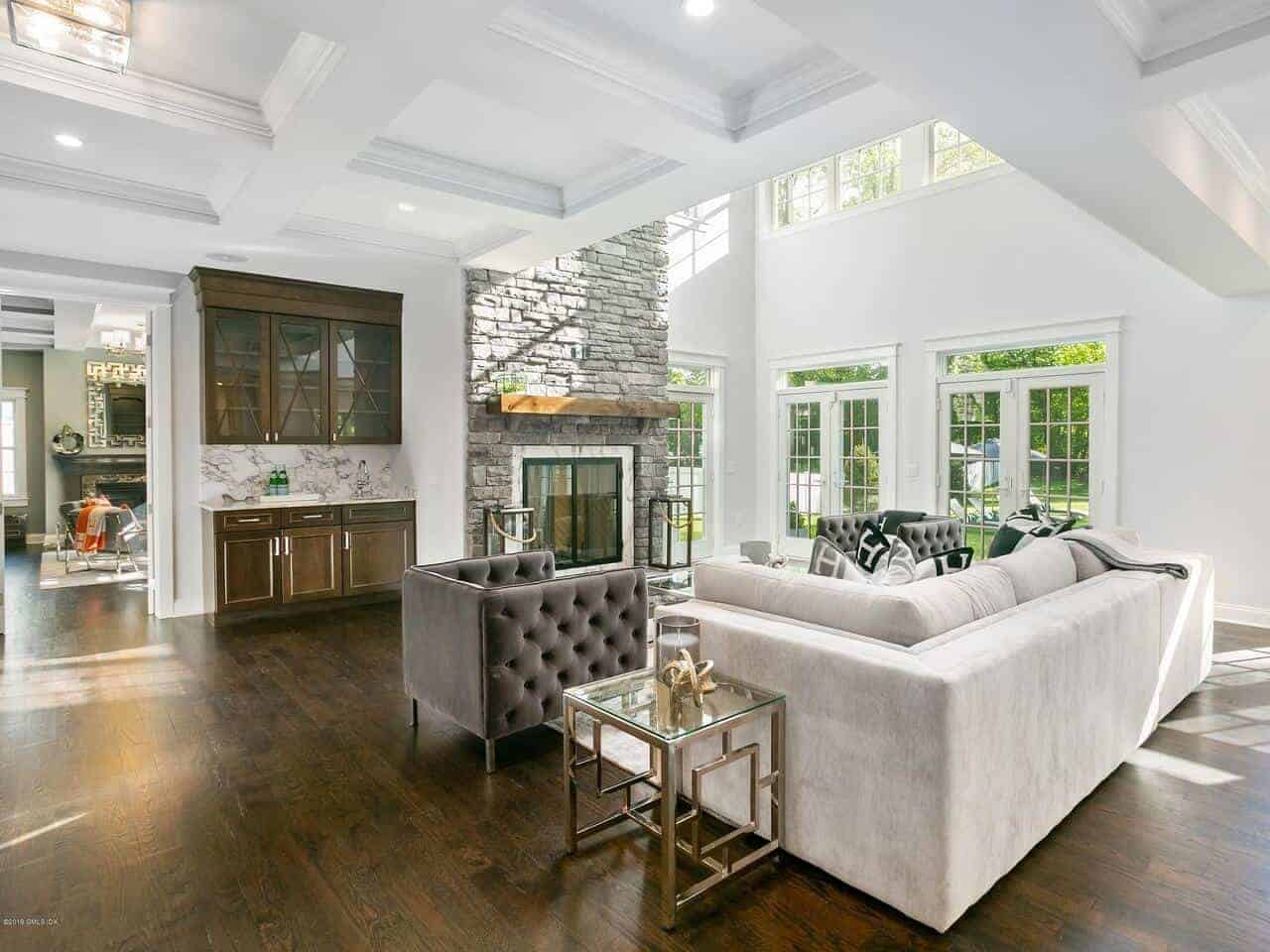 The dark hardwood flooring of this charming living room is a nice contrast for the white coffered ceiling that opens up to a section with a high ceiling and walls filled with tall windows and doors illuminating the fireplace and the sofa set.