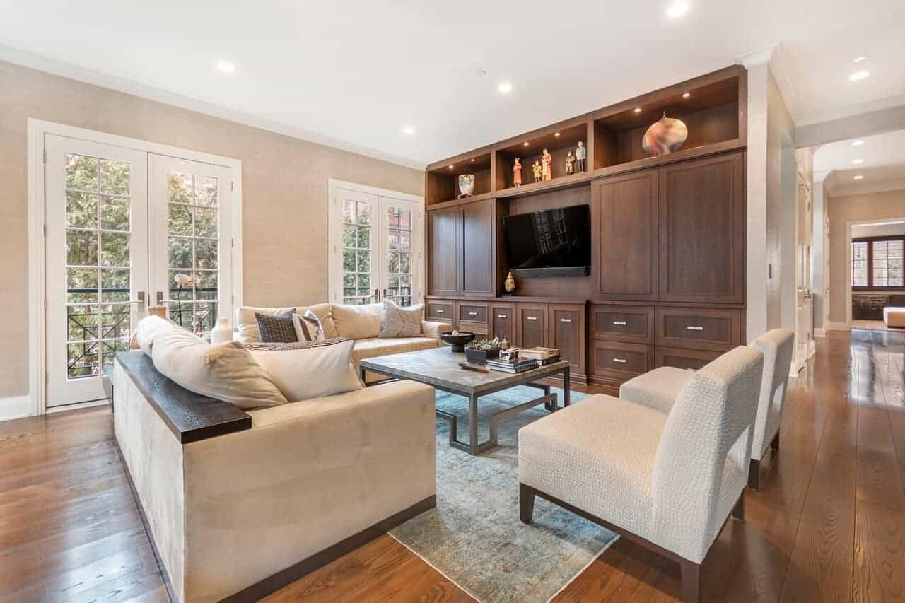 This living room has beige sofas and cushioned chairs facing a glass-top table by the TV that is mounted on a large wooden structure dominating the wall with built-in cabinets and drawers blending with the hardwood flooring.