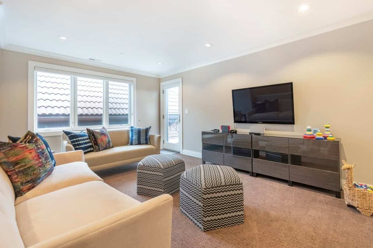 The beige carpeted flooring matches with the beige walls and sofas that have colorful throw pillows. These beige elements are contrasted by the wooden console table with cabinets that matches the TV mounted on the wall above.