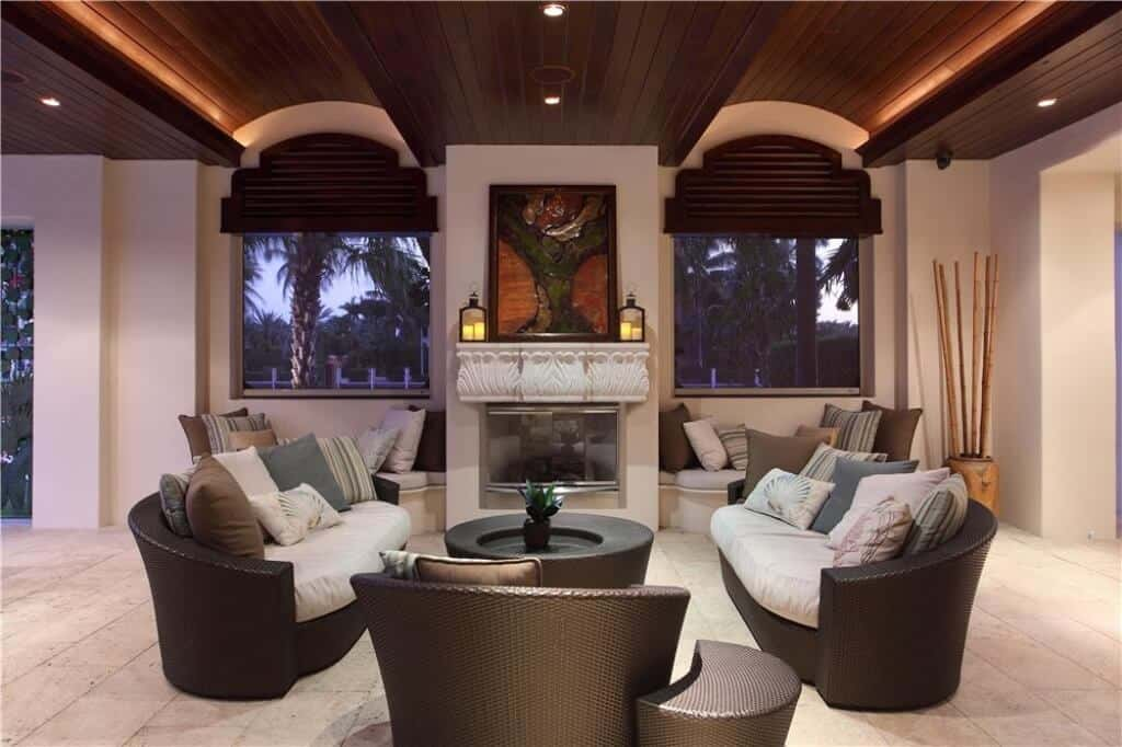 The matching dark woven wicker sofa set stands out against the beige marble flooring of this elegant living room that has a fireplace in the middle two dome windows paired with an irregular wooden ceiling.
