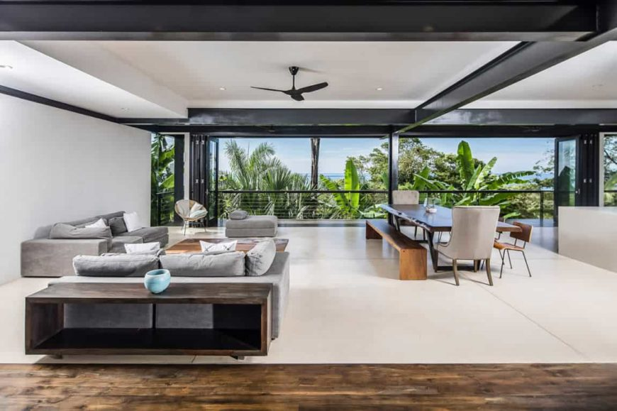 This living room area is a part of a large room that also houses the dining area beside it. The gray velvet cushioned sofas and its wooden coffee table stands out against the white walls, ceiling and floors that brings the focus to the lovely and lush treetop scenery outside the folding glass doors.