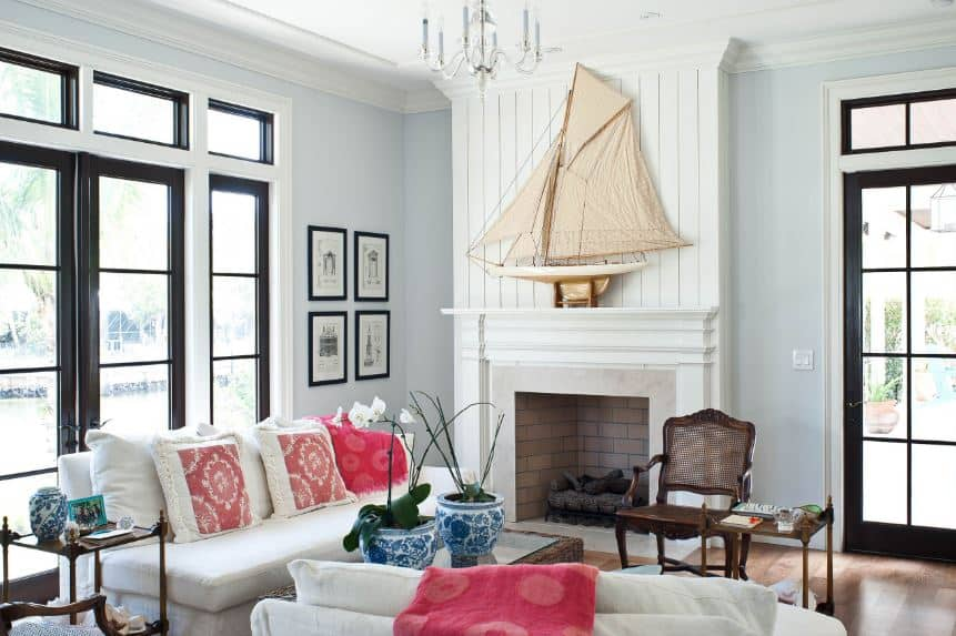 There is a large decorative sail boat model mounted above the white mantle of the fireplace. This column that houses the fireplace matches the white sofas paired with pink pillows and blankets. The woven wicker glass-top coffee table pairs well with the hardwood flooring.