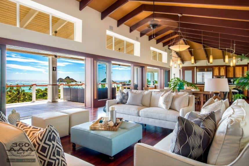 This Tropical-style living room has redwood flooring matching the exposed wooden beams of the high cathedral ceiling. This redwood flooring makes the light beige sofa set stand out as it matches the light beige walls illuminated by the natural lights.