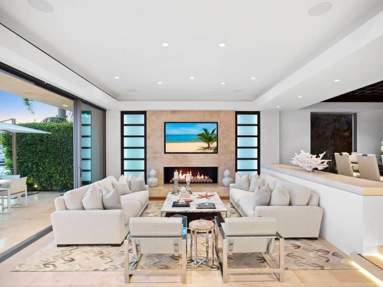 This bright living room is dominated by the light gray and light beige tones that brightens from the natural lights coming in from the open wall of sliding glass doors. This is augmented by the modern fireplace topped with the TV and flanked by frosted glass panels.