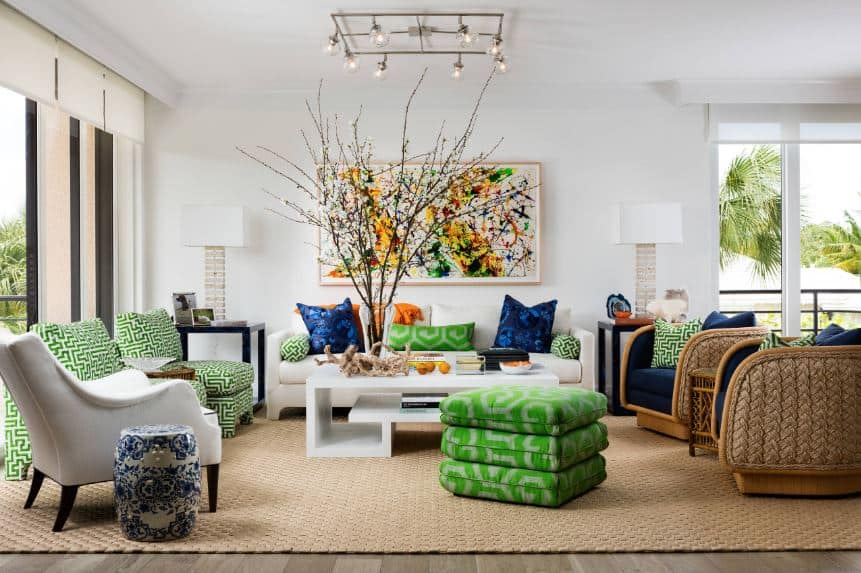 This charming and colorful Tropical-style living room has green patterned cushions on its chairs and pillows. This is complemented by the green cushions of the woven wicker chairs and the other pillows. These varying colors are mirrored by the abstract painting that stands out against the white walls.