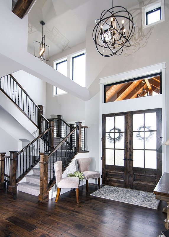 French entry door that matches the dark hardwood flooring and railings add a rustic touch to this craftsman-style foyer.