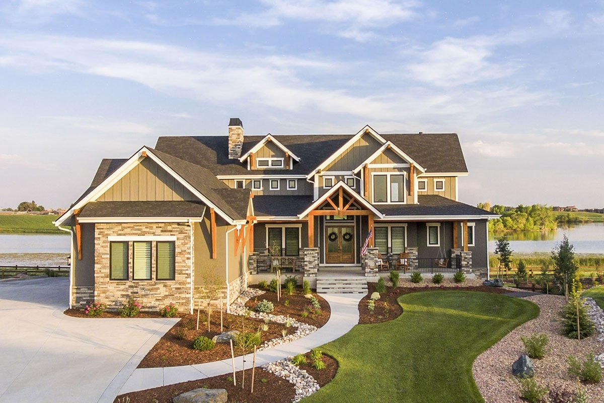 Richly textured craftsman home with a well-maintained garden featuring small shrubs, pebble accents, a curved walkway, and a luscious lawn.