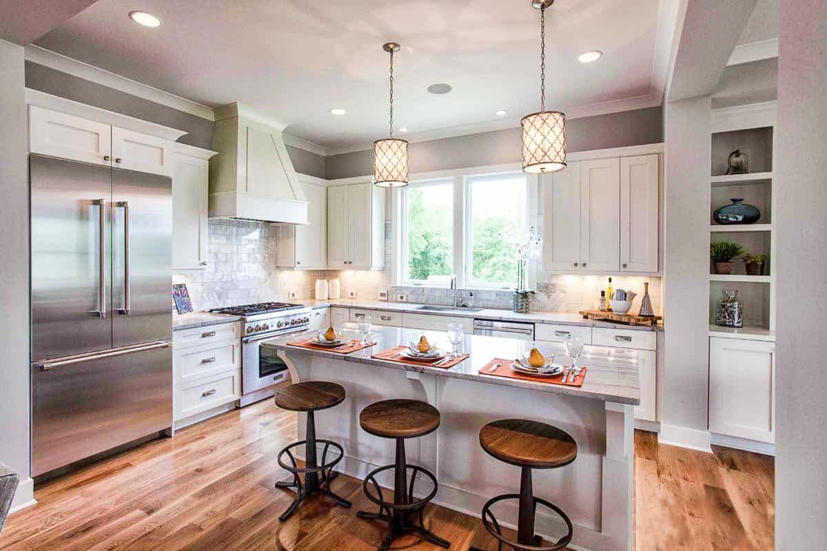 The kitchen is equipped with stainless steel appliances, white cabinetry, and a breakfast island complemented by round bar stools and a pair of glass pendants. These are all then complemented by the dark hardwood flooring.
