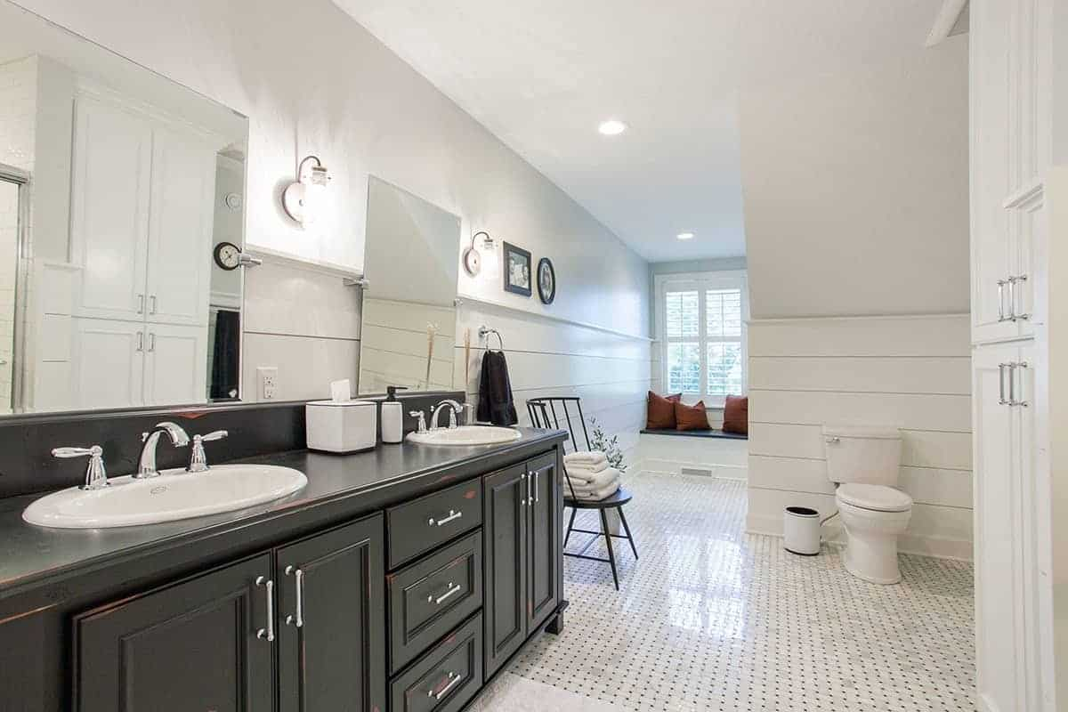 The dark wooden cabinets and drawers of the two-sink vanity stands out against the light beige tones of the floor tiles, walls and ceiling that has recessed lights.