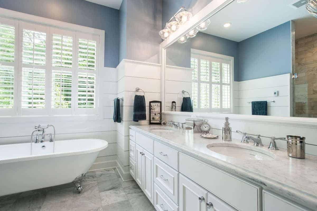 This bathroom has a freestanding bathtub under the white shuttered window on the far wall. This white window blends well with the wainscoting and the white white vanity.