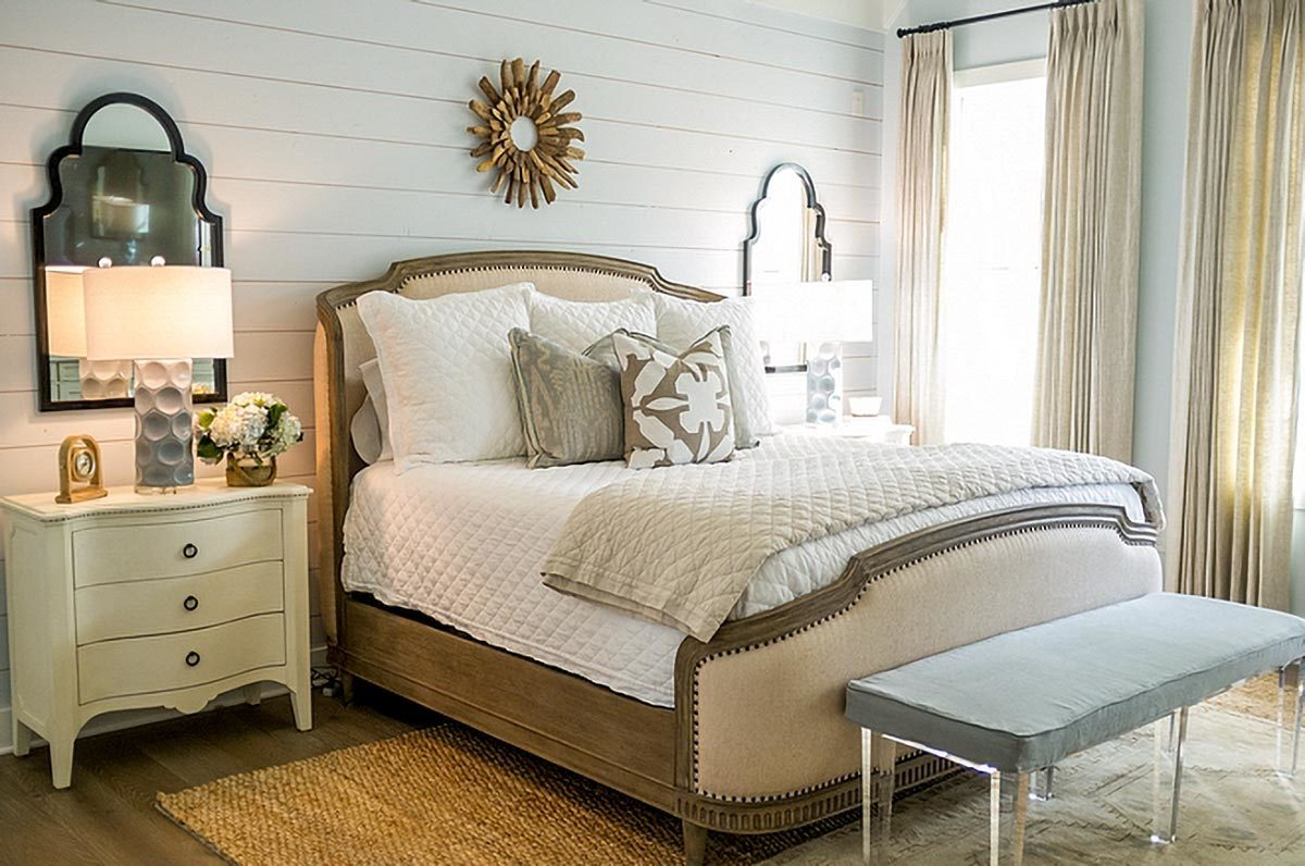 This primary bedroom features a cushioned bench supported by glass legs and a white shiplap accent wall adorned by sunburst artwork and arched mirrors.