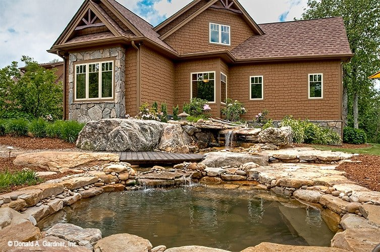 Stone accents in the cedar shake home reflect the stunning man-made pond that's graced with waterfall features and a wood plank deck.
