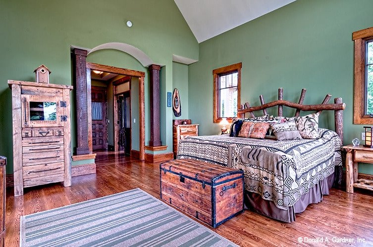 This primary bedroom is furnished with rustic cabinets, a unique wood log bed, and trunk chest storage. An alcove on the left side adorned by wooden columns leads to the primary bath and walk-in closet.