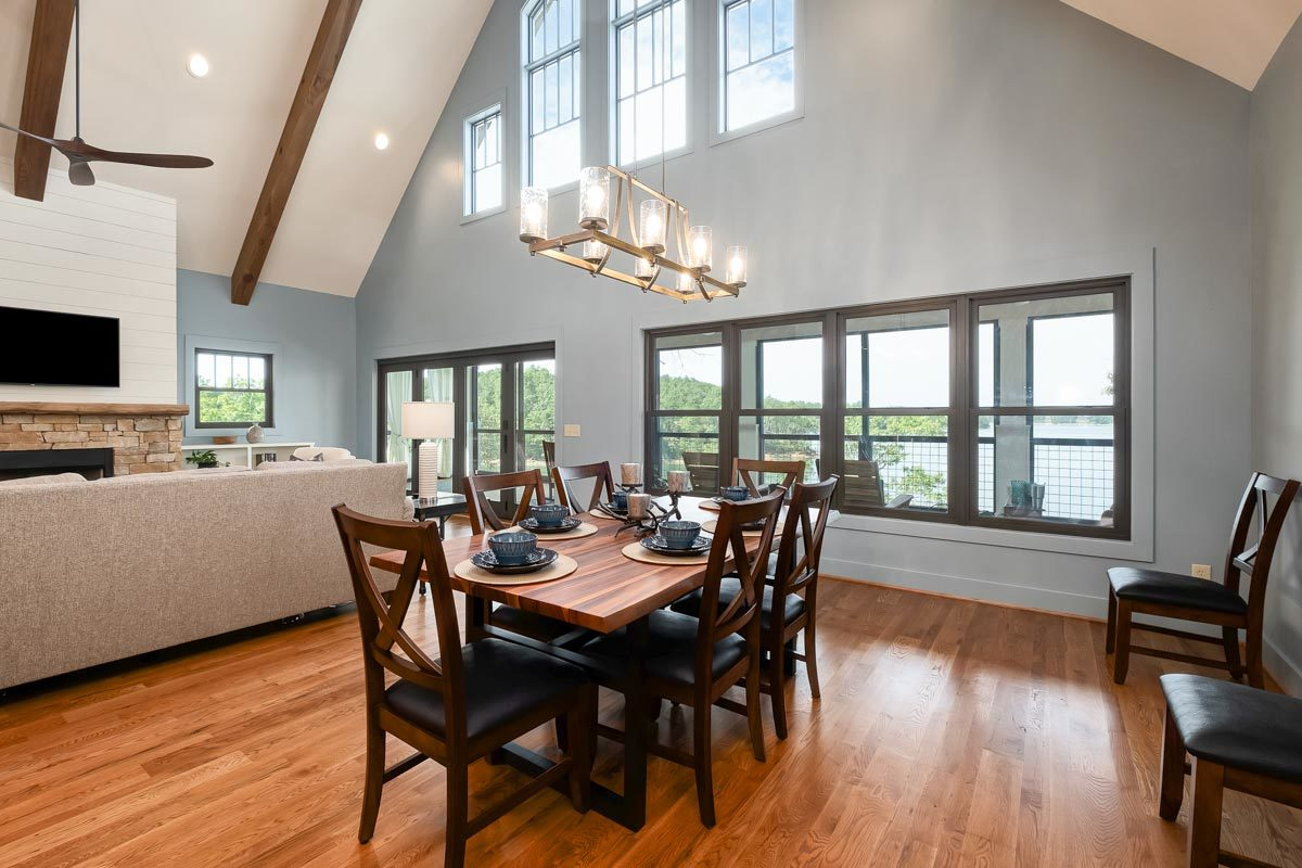 This dining room offers leather cushioned chairs and a wooden dining table that matches the hardwood flooring. It is well-lit by a linear chandelier that hags from the high cathedral ceiling.