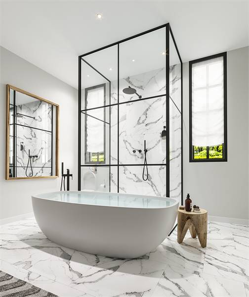 Scandinavian-style bathroom with a freestanding tub and a walk-in shower fitted with wrought iron fixtures. The white marble tile flooring is echoed in the shower's backsplash creating a seamless flow.