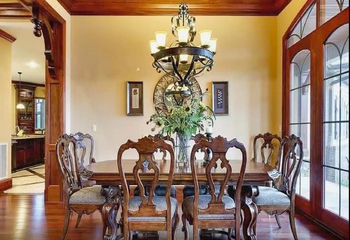 This kitchen radiates a classic vibe with its wrought iron chandelier, a wooden dining table, and matching chairs with intricate detailing.