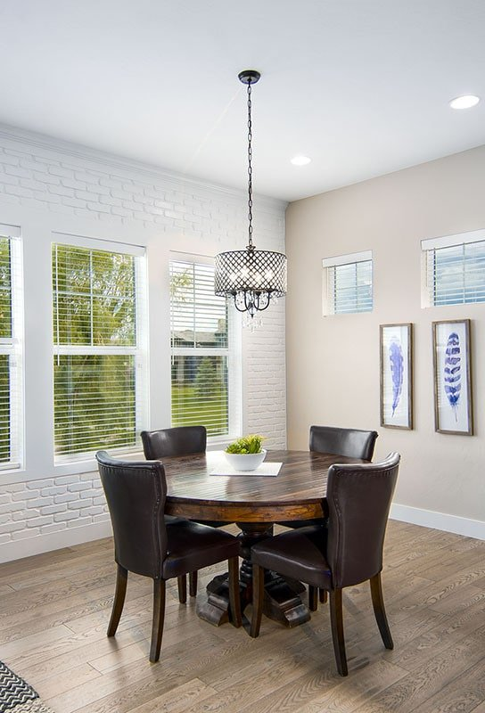White brick walls create a stunning contrast to the leather upholstered chairs and round dining table with a dark wood tone.