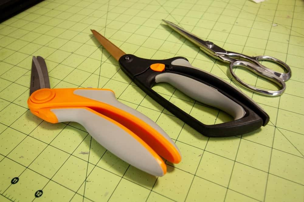 Three types of scissors on a cutting mat.