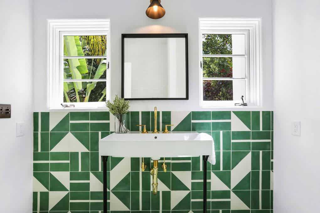 This is the vanity area of a Spanish-Style bathroom with a brass wall-mounted sconce above the square vanity mirror that is flanked by French windows. The vibrant green mosaic tiles are a good reflection of the scenery outside the windows and are a good contrast for the brass faucet and pipes.