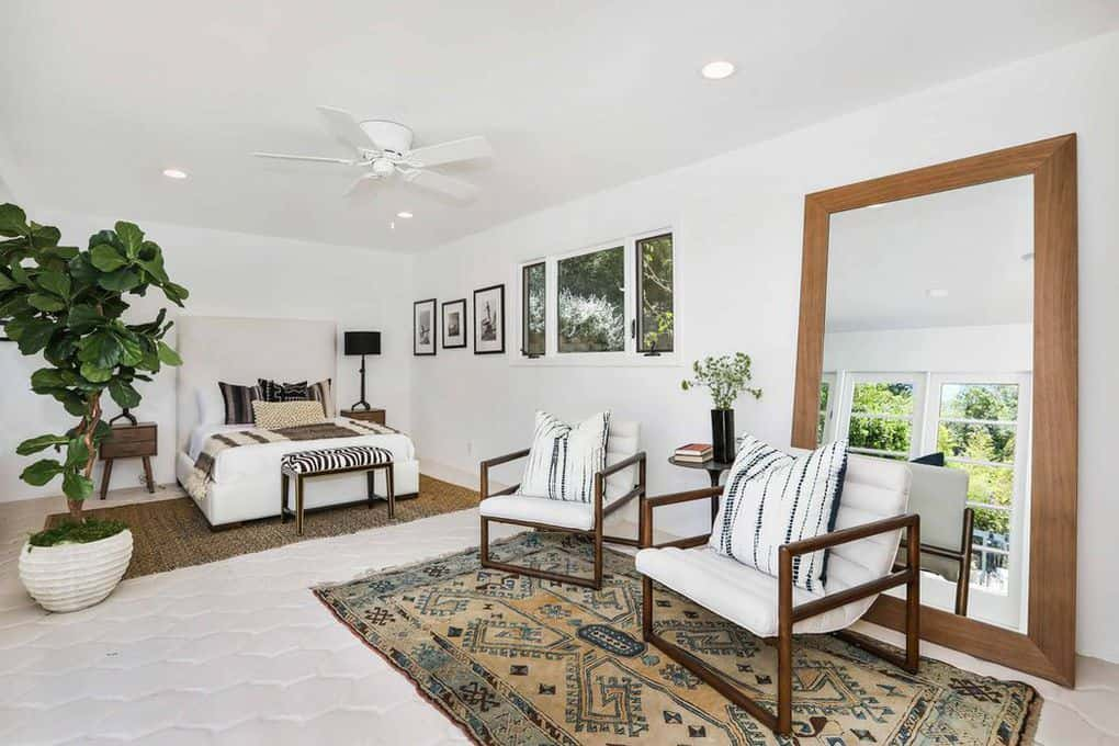 This Spanish-Style bedroom has an abundance of patterns from its area rugs, pillows and the bench at the foot of the bed. The indoor plant and massive mirror add a certain vibrancy to the white walls and white ceiling with pin lights at the corners and a white ceiling fan.