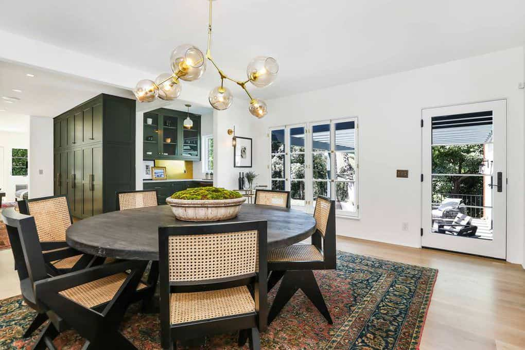 The Sputnik chandelier lightens up this predominantly white Spanish-Style dining room augmented by the natural light coming from the French windows and glass door. A round wooden dining table is surrounded by six dark wooden chairs with woven wicker over a colorful patterned area rug.