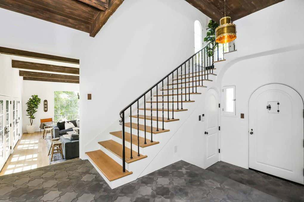 Spanish-Style foyer with a patterned gray stone flooring that properly transitions from the exterior to the interior of the house and its wooden floor. The white walls and the main door are illuminated by golden pendant lighting that hangs from a wooden ceiling with exposed beams.