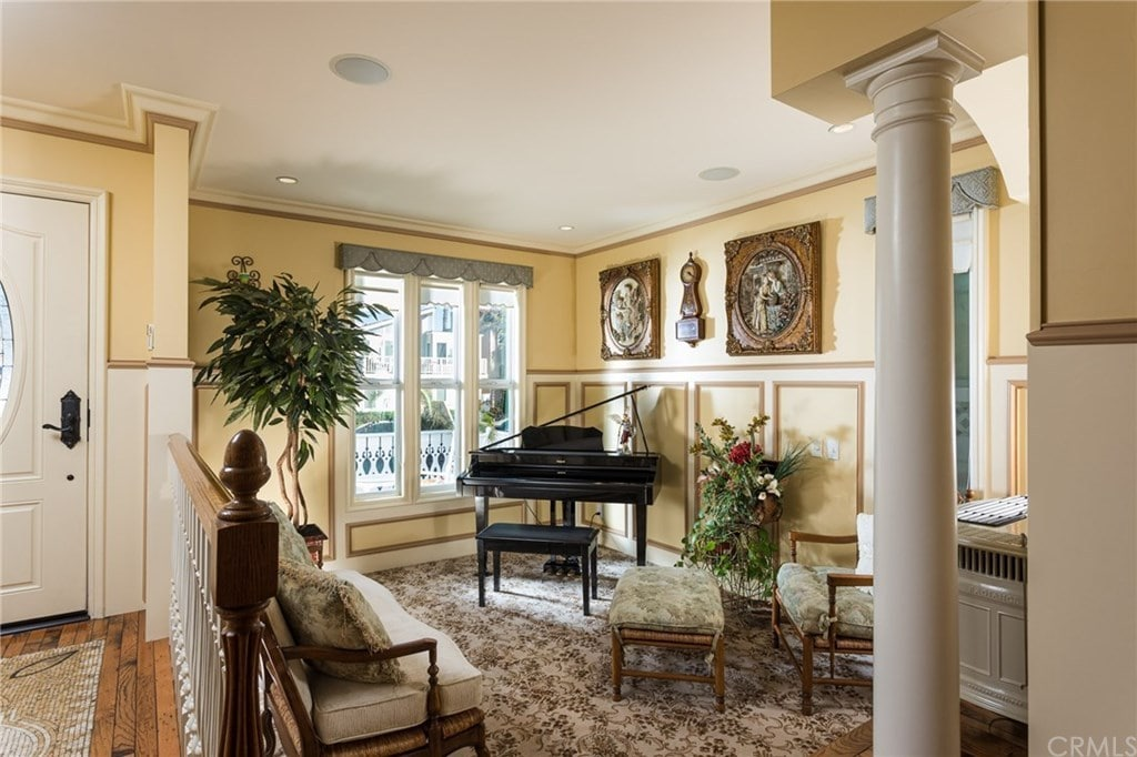 This living room is decorated with fresh plants and carved wood wall arts mounted above the beige wainscoting. It features cozy seats and a baby grand piano by the glass paneled windows dressed in a charming dotted valance.
