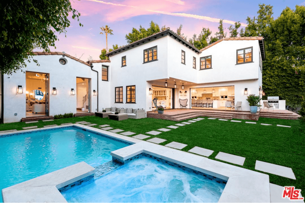 This is a Spanish-style home with traditional elements that are balanced with the straight lines and angles of a modern house. The modern pool in the backyard is bordered with brilliant white stone steps on a nice carpet of grass that beautifully contrasts the white walls. Illumination is provided by several Spanish style lanterns mounted on walls and patio ceiling.