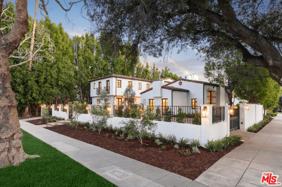A brilliant low wall surrounds this Spanish home that has warm lighting from its matching wall-mounted lanterns. these lanterns seem to mirror the yellow-lit French windows and French glass doors that present a perfect partner for the clay-tiled roofs and a modern-style chimney.
