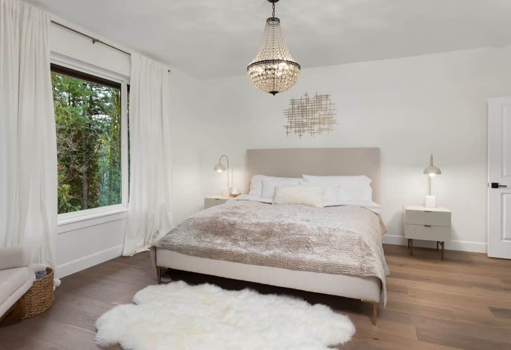 The brightness of the white walls and ceiling are counterbalanced with a hardwood flooring topped with a white fur area rug at the foot of the bed that has gray sheets. The gray cushioned headboard is flanked by two bright table lamps and topped with nice wall art.