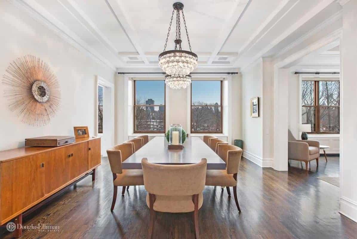 Large dining area with white walls and hardwood flooring, along with a stylish white ceiling lighted by a fancy chandelier.