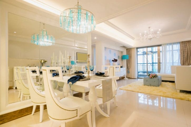 A dining space featuring a white dining table and chairs set lighted by a fancy chandelier.