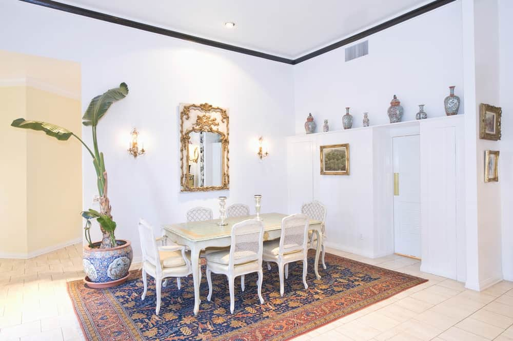 A dining area featuring a classy area rug, where the dining table and chairs are set. The space is surrounded by white walls and white tiles flooring.