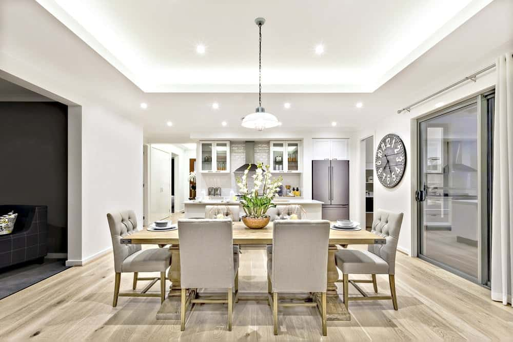 White dine-in kitchen featuring a brown dining table with gray chairs set on the hardwood flooring.