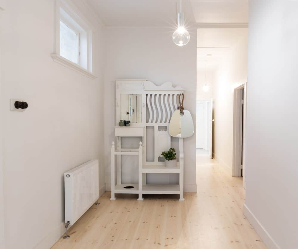 This is a view from the door of this white foyer with white walls and a white ceiling that supports a pendant light illuminating the hardwood floors. There is a quaint white wooden structure once you enter this foyer that has multiple purposes like a shoe rack and umbrella rack.