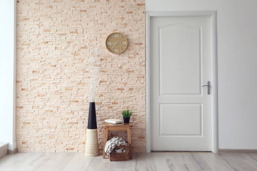 This white foyer has two distinct walls flanking the white main door. One wall is as white as the door and seems to blend with it while the other is made of beige stone bricks and accented with a small wooden chair with a wooden crate beneath for coats or shoes.