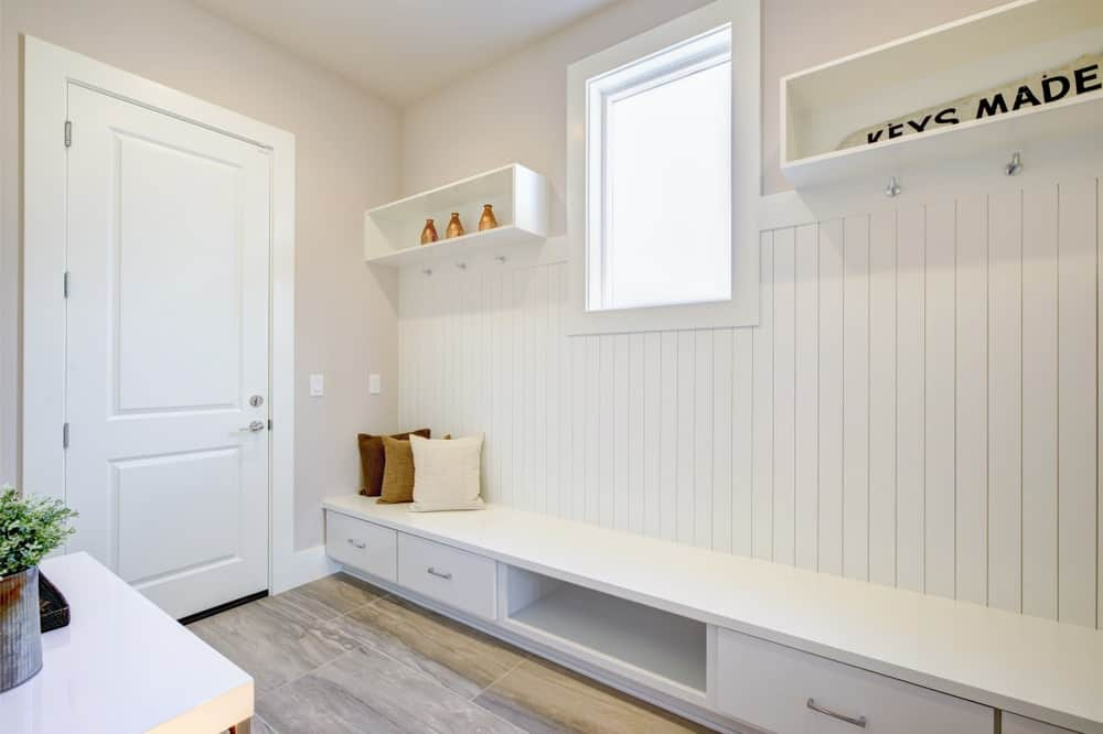This is a white foyer that has a nice mudroom attached to the white wall. It has a long and low built-in wooden drawer that acts as a shoe rack and bench. Above it are hanging white shelves that has hooks attached for coats and hats.