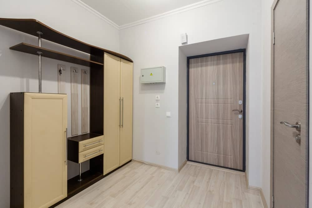 This white foyer with white walls and the white ceiling is dominated by an elegant large wooden structure with built-in cabinets and drawers for coat storage and it has a shoe rack at the bottom. The door has the same hue as the hardwood flooring to serve as a good background for this structure.