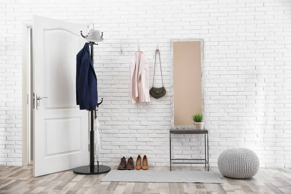 The white wooden main door is paired with textured white walls made of stone bricks and a hardwood flooring of grayish hue. This is topped with a light gray area rug beside the dark iron coat and hat rack by the door. There is also a chic woven beanbag chair beside a small metallic table for accent.