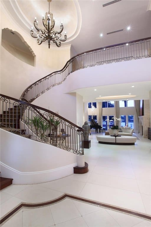 A mansion with a white foyer featuring white tiles flooring with a brown accent, lighted by a glamorous chandelier.