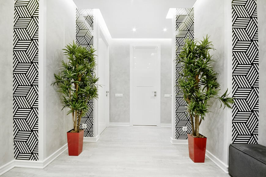 A white foyer featuring stylish wall designs added by green potted plants adding color to the white area.