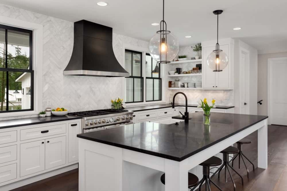 This charming and elegant kitchen has a delicate balance of white and black elements that are mediated by the hardwood flooring. The countertops of both kitchen island and L-shaped peninsula are both black contrasting against their white cabinetry.
