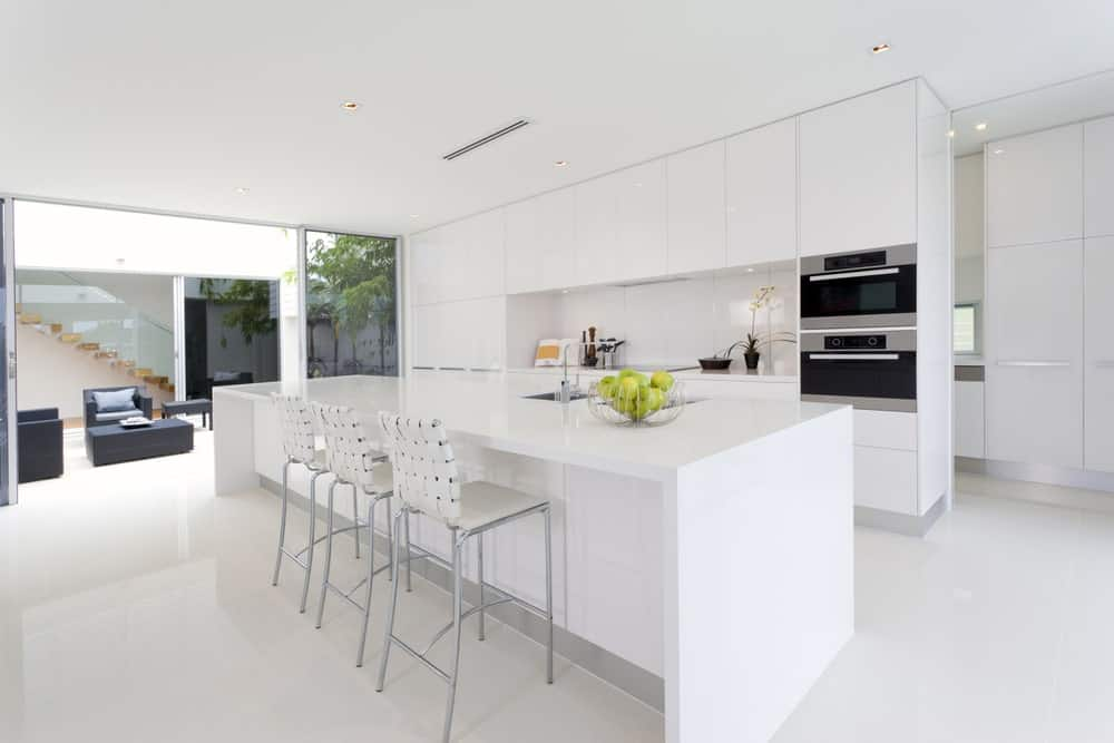 The uniformity and simple white brightness of this kitchen are almost clinical in its white monotony. This is slightly subdued by the modern ovens and the modern steel stools of the white kitchen island. This is also balanced by the outside views of the massive glass doors.